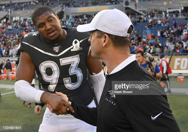 Calais Campbell of the Jacksonville Jaguars shakes hands with Head Coach John Harbaugh of the AFC after the 2020 NFL Pro Bowl at Camping World...