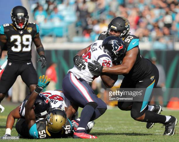 Calais Campbell of the Jacksonville Jaguars tackles Lamar Miller of the Houston Texans during the second half of their game at EverBank Field on...