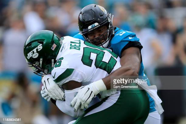 Calais Campbell of the Jacksonville Jaguars tackles Le'Veon Bell of the New York Jets during the game at TIAA Bank Field on October 27, 2019 in...