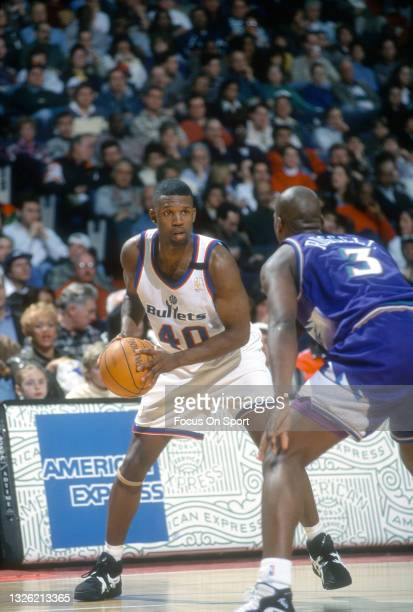 Calbert Cheaney of the Washington Bullets looks to put a move on Bryon Russell of the Utah Jazz during an NBA basketball game circa 1997 at US...