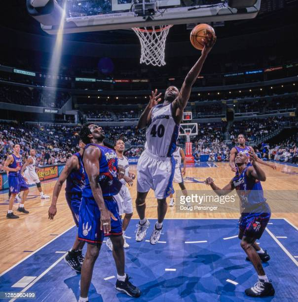 Calbert Cheaney, Shooting Guard for the Washington Wizards makes a one handed lay up to the basket over Dee Brown and Charles Oakley of the Toronto...