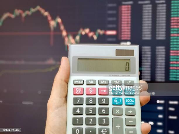 calculating on calculator with a business graph on the computer screen. - cristian neri foto e immagini stock