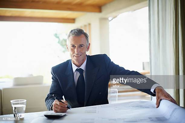 calculating the costs involved in his planning - handsome 50 year old men stock photos and pictures