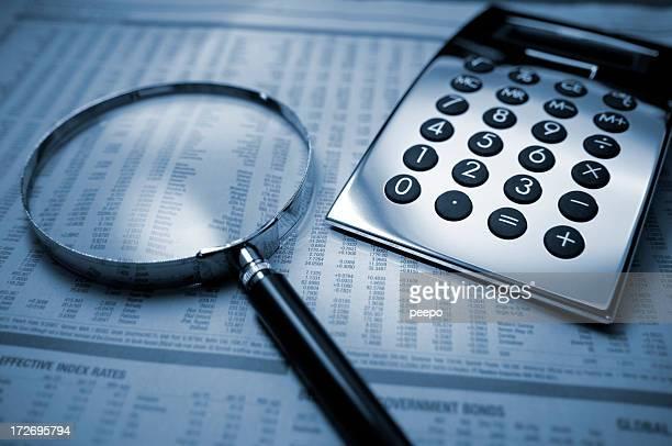 Rechner und Lupe auf finanzielle Zeitung