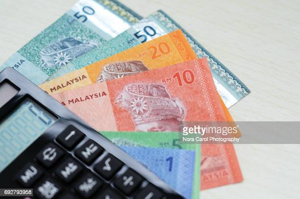 calculator and malaysian ringgit currency - malaysian ringgit stock photos and pictures