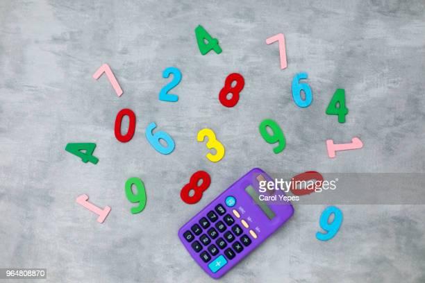 calculator and numbers top view in grey background - cifras financieras fotografías e imágenes de stock
