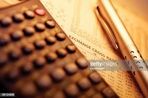 Calculator and pen on top of currency exchange rate information, close-up