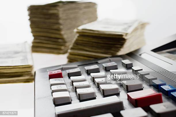 Calculator and stacks of banknotes