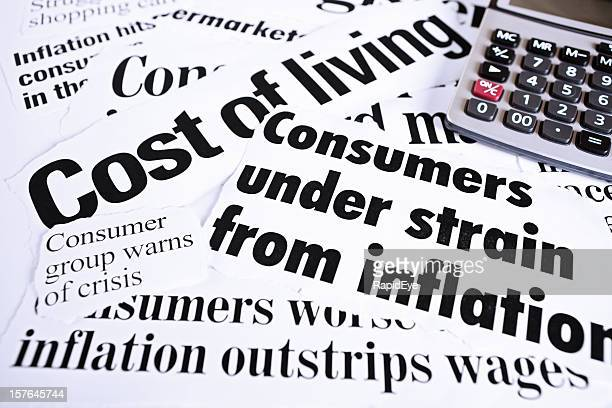Calculator on newspaper headlines about cost of living and inflation