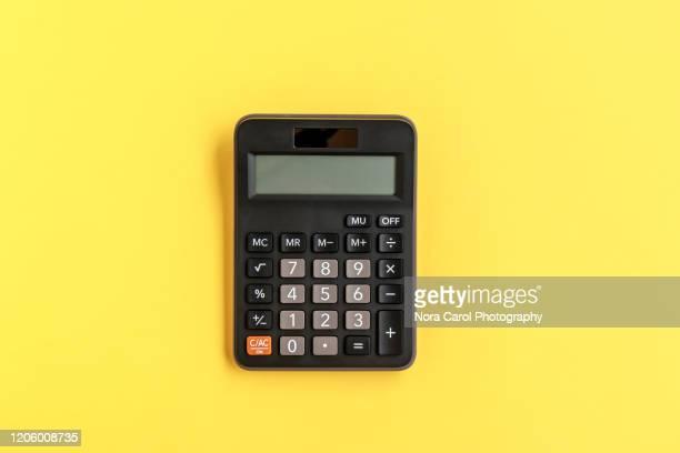 calculator on yellow background - taschenrechner stock-fotos und bilder
