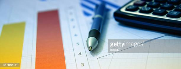 calculator, pen and financial papers