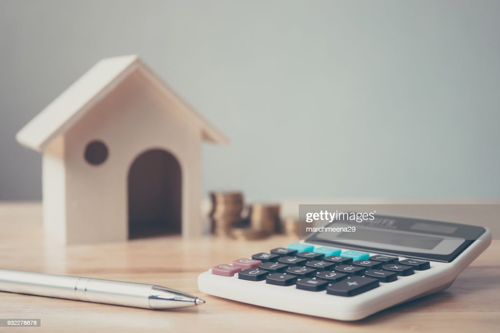 Calculator with wooden house and coins stack and pen on wood table. Property investment and house mortgage financial concept : Stock Photo