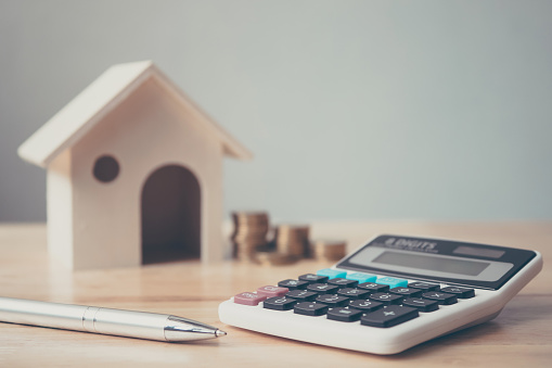 Calculator with wooden house and coins stack and pen on wood table. Property investment and house mortgage financial concept 932278678