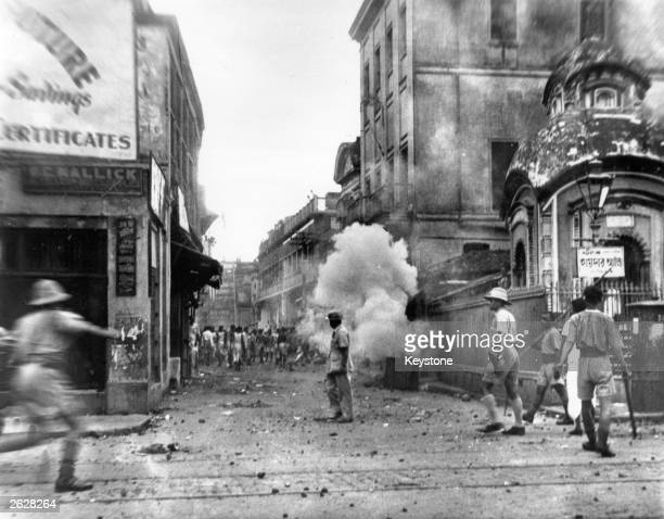 Calcutta policemen use tear gas bombs during the communal riots in the city. The communal riots lasted 5 days; at least 2,000 were killed, and over...