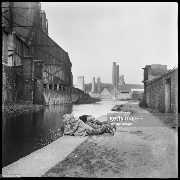 Caldon Canal, Joiner's Square, Hanley, Stoke-on-Trent, Staffordshire, 1965-1968. Children lying on the towpath looking into the waters of the Caldon...