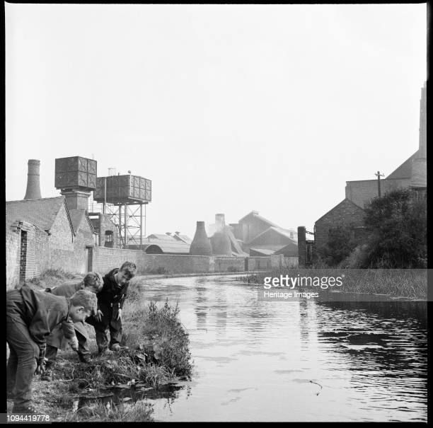 Caldon Canal, Joiner's Square, Hanley, Stoke-on-Trent, Staffordshire, 1965-1968. Three boys scrutinizing the waters of the Caldon Canal from a point...