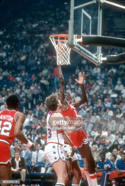 Caldwell Jones of the Philadelphia 76ers goes up to shoot over Jeff Ruland of the Washington Bullets during an NBA basketball game circa 1982 at the...