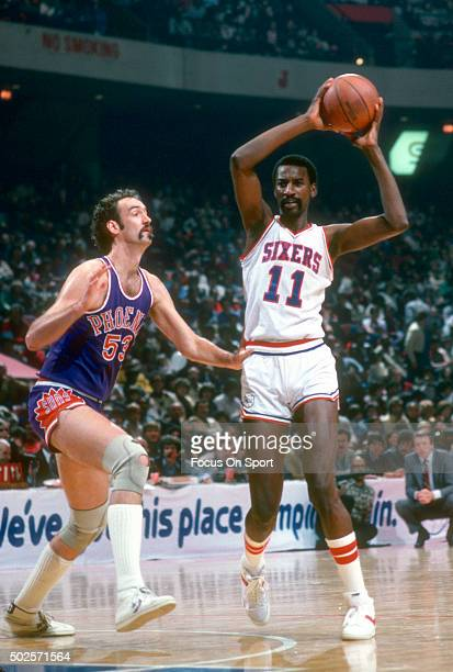 Caldwell Jones of the Philadelphia 76ers looks to pass the ball over the top of Rich Kelley of the Phoenix Suns during an NBA basketball game circa...