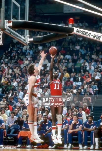 Caldwell Jones of the Philadelphia 76ers shoots over Jeff Ruland of the Washington Bullets during an NBA basketball game circa 1982 at the Capital...