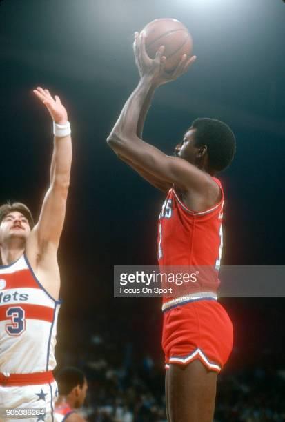 Caldwell Jones of the Philadelphia 76ers shoots over Jeff Ruland of the Washington Bullets during an NBA basketball game circa 1981 at the Capital...