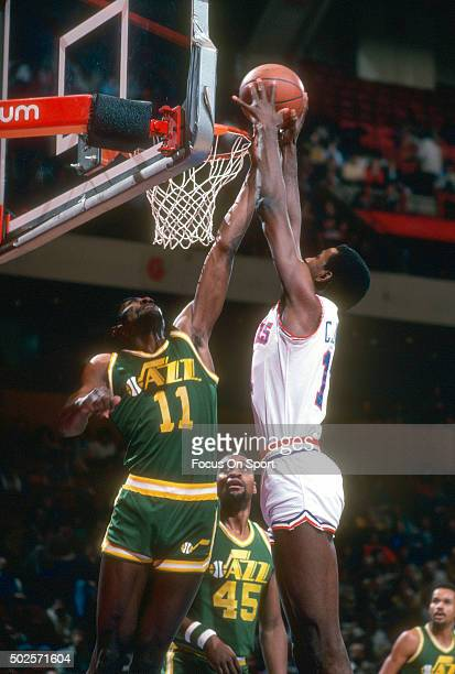 Caldwell Jones of the Philadelphia 76ers slam dunks over James Hardey of the New Orleans Jazz during an NBA basketball game circa 1982 at The...