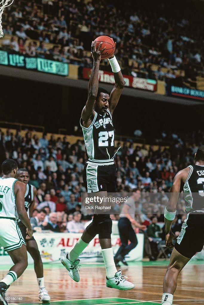 Caldwell Jones #27 of the San Antonio Spurs rebounds against the Boston Celtics during a game played in 1990 at the Boston Garden in Boston, Massachusetts.