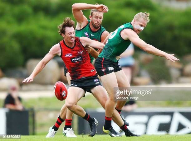 Cale Hooker and Jake Stringer compete for the ball against Mitch Brown during the Essendon Bombers AFL IntraClub Match at The Hangar on February 10...