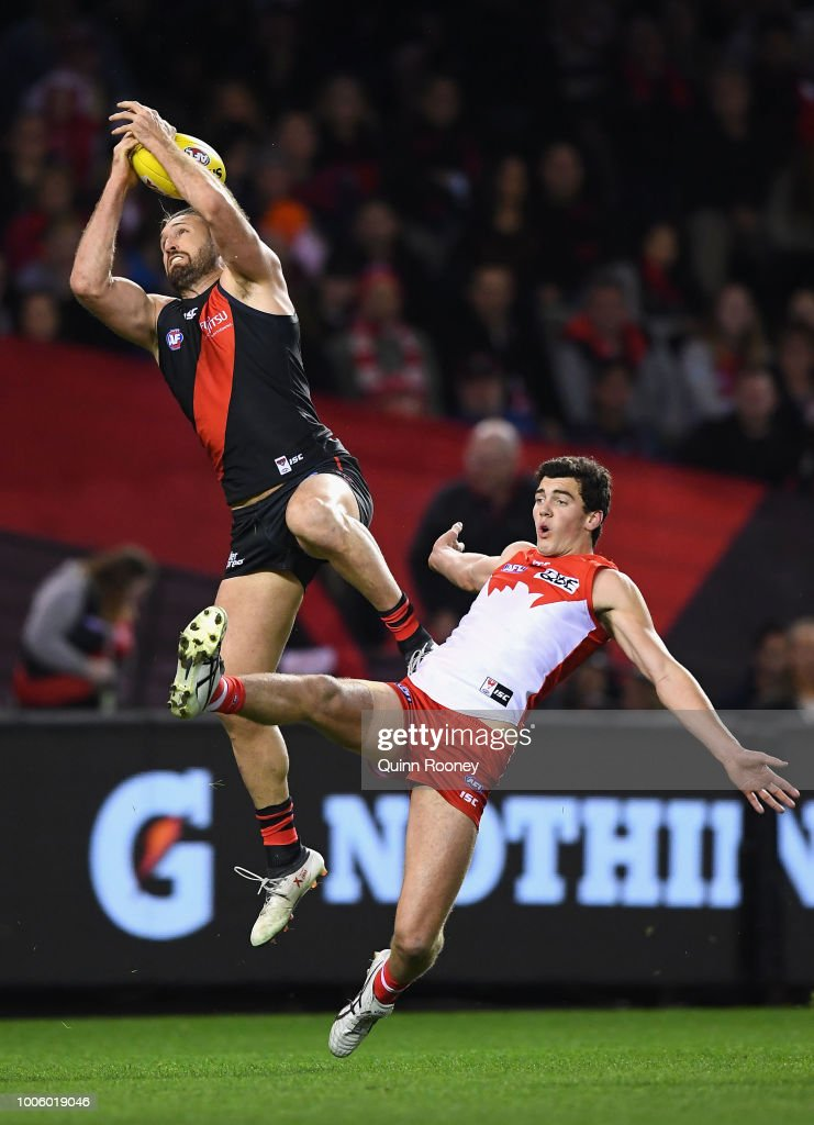 Cale Hooker of the Bombers marks over the top of Tom McCartin of the Swans during the round 19 AFL match between the Essendon Bombers and the Sydney Swans at Etihad Stadium on July 27, 2018 in Melbourne, Australia.