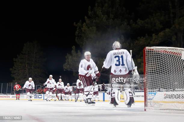 Cale Makar of the Colorado Avalanche congratulates goaltender Philipp Grubauer after defeating the Vegas Golden Knights in the 'NHL Outdoors At Lake...