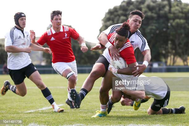 Caleb Cavubati of the New Zealand Schools Barbarians is tackled by Jordan ThompsonDunn of New Zealand Under 18 Maori on his way to scoring a try...