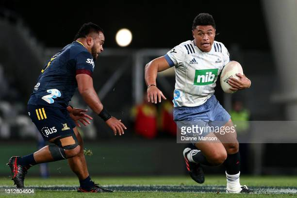 Caleb Clark of the Blues is challenged by Siate Tokolahi of the Highlanders during the round eight Super Rugby Aotearoa match between the Highlanders...