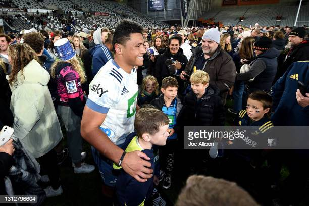 Caleb Clark of the Blues poses for a photo with a fan during the round eight Super Rugby Aotearoa match between the Highlanders and the Blues at...
