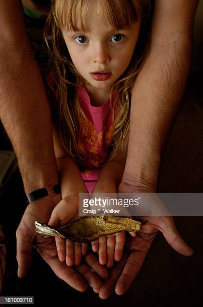 Caleb Dillon and his 4 year old daughter Kailynn display a piece of shrapnel that nearly killed Dillon in Iraq at their home on Post at Fort Carson...