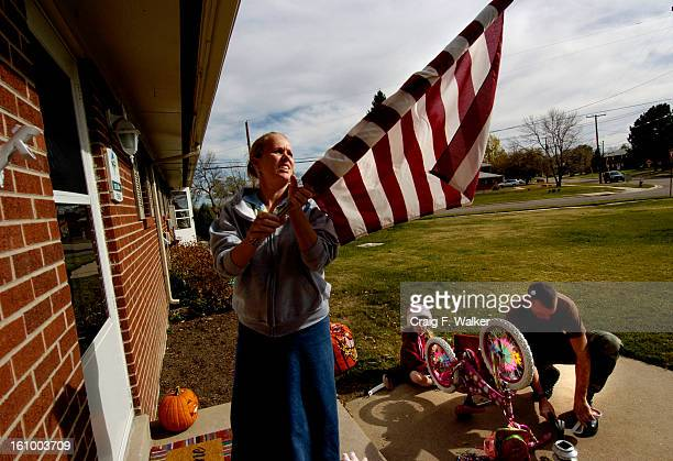 Caleb Dillon works on his daughters bike while his wife Jennie puts out the flag at their home on Post at Fort Carson Earlier he spoke about their...