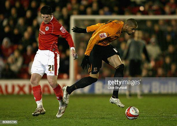 Caleb Folan of Hull City is tackled byJon Macken of Barnsley during the CocaCola Championship match between Barnsley and Hull City at Oakwell on...