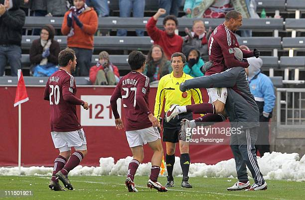 Caleb Folan of the Colorado Rapids leaps into the arms of a teammate as he celebrates his goal in the first half against D.C. United along with...