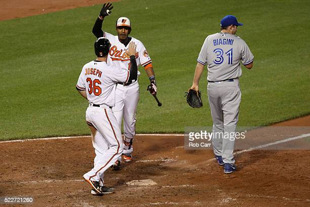 Caleb Joseph of the Baltimore Orioles celebrates scoring the winning run on a passed ball thrown by Joe Biagini of the Toronto Blue Jays with...