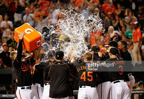 Caleb Joseph of the Baltimore Orioles dumps water on Manny Machado after Machado hit a walk off two RBI home run to give the Orioles an 86 win the...