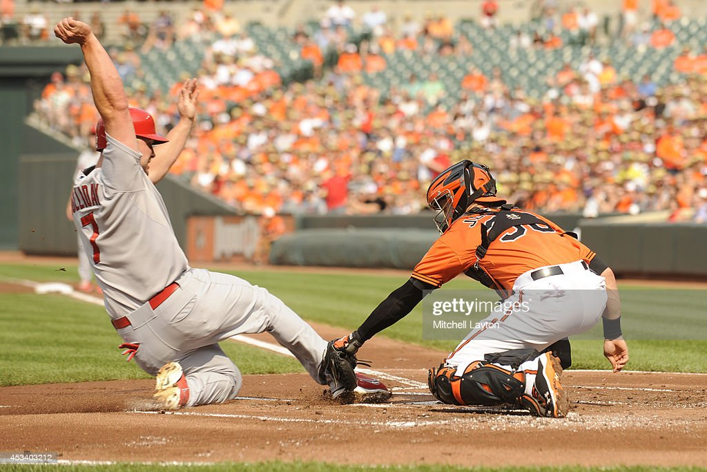 Caleb Joseph #36 of the Baltimore Orioles tags out Matt Holliday #7 of the St. Louis Cardinals at the plate on a ball hit by Jhonny Peralta #27 (not pictured) in the first inning during a baseball game on August 9, 2014 at Oriole Park at Camden Yards in Baltimore, Maryland.