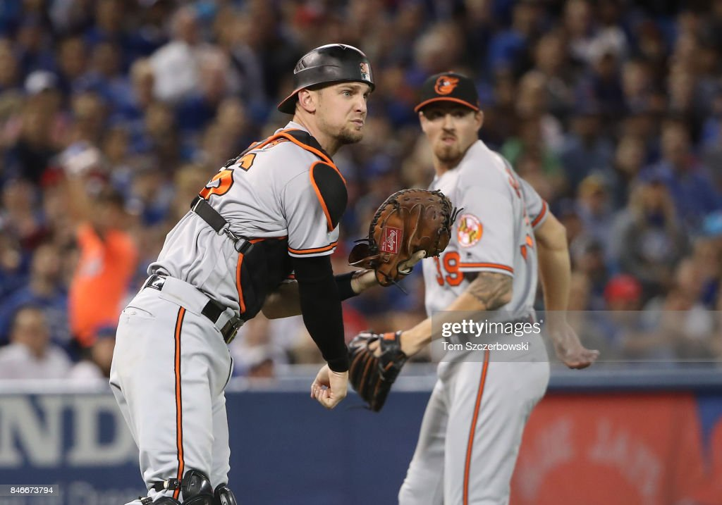 Caleb Joseph #36 of the Baltimore Orioles throws out the baserunner as Kevin Gausman #39 watches in the third inning during MLB game action as Ryan Goins #17 of the Toronto Blue Jays successfully executes a sacrifice at Rogers Centre on September 13, 2017 in Toronto, Canada.