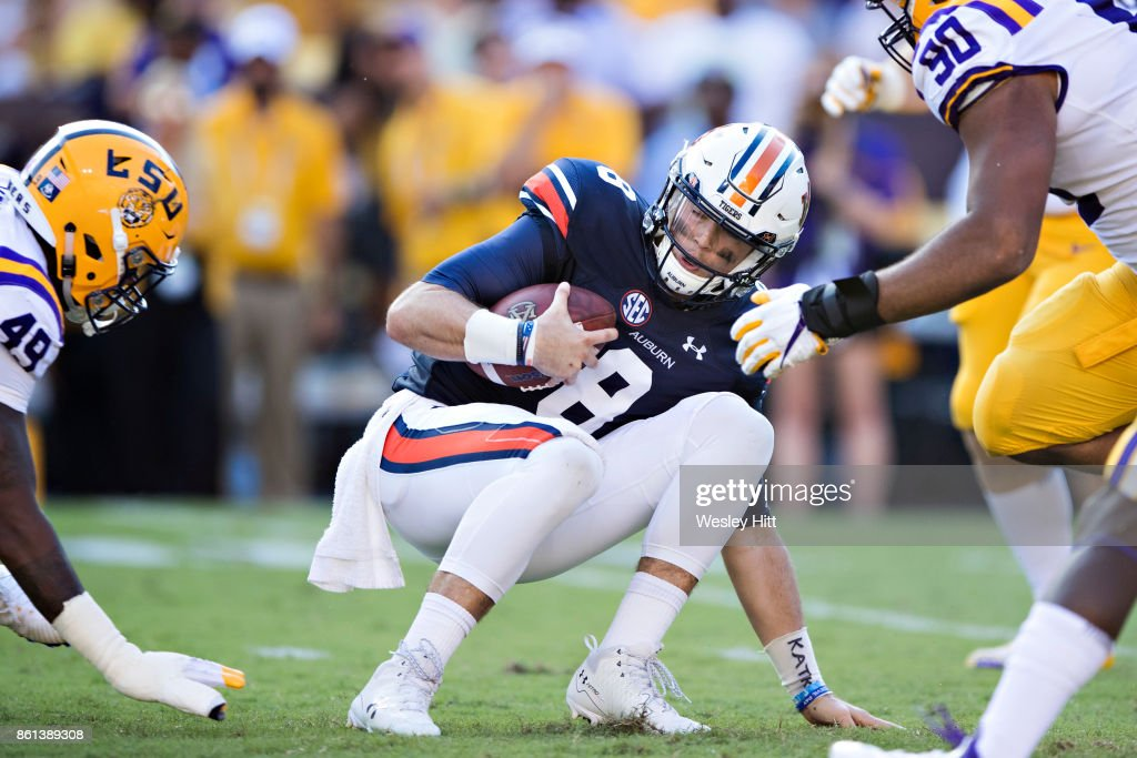 Caleb Lewis #8 of the Auburn Tigers is hit after running the ball by Arden Key #49 and Rashard Lawrence #90 of the LSU Tigers at Tiger Stadium on October 14, 2017 in Baton Rouge, Louisiana. The LSU defeated the Auburn 27-23.