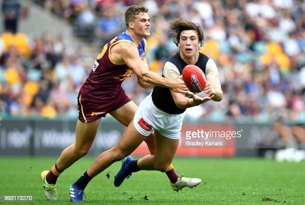 Caleb Marchbank of Carlton gets a handball away during the round 16 AFL match between the Brisbane Lions and the Carlton Blues at The Gabba on July 7...