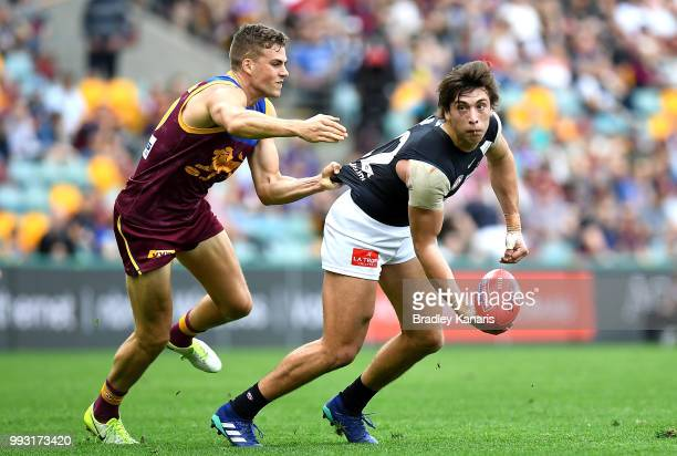 Caleb Marchbank of Carlton is pressured by the defence of Tom Cutler of the Lions during the round 16 AFL match between the Brisbane Lions and the...