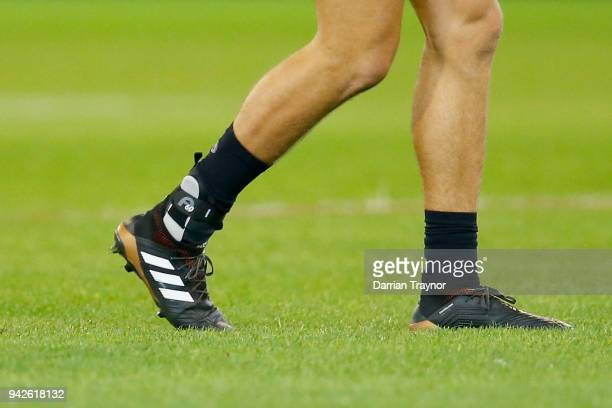 Caleb Marchbank of the Blues comes back onto the ground with an ankle brace on his injured root foot during the round three AFL match between the...