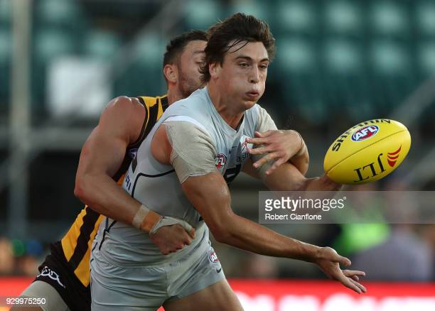 Caleb Marchbank of the Blues handballs during the JLT Community Series AFL match between the Hawthorn Hawks and the Carlton Blues at the University...