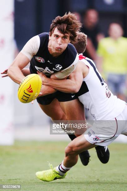 Caleb Marchbank of the Blues handballs from Jack Lonie of the Saints during the JLT Community Series AFL match between the Carlton Blues and the St...