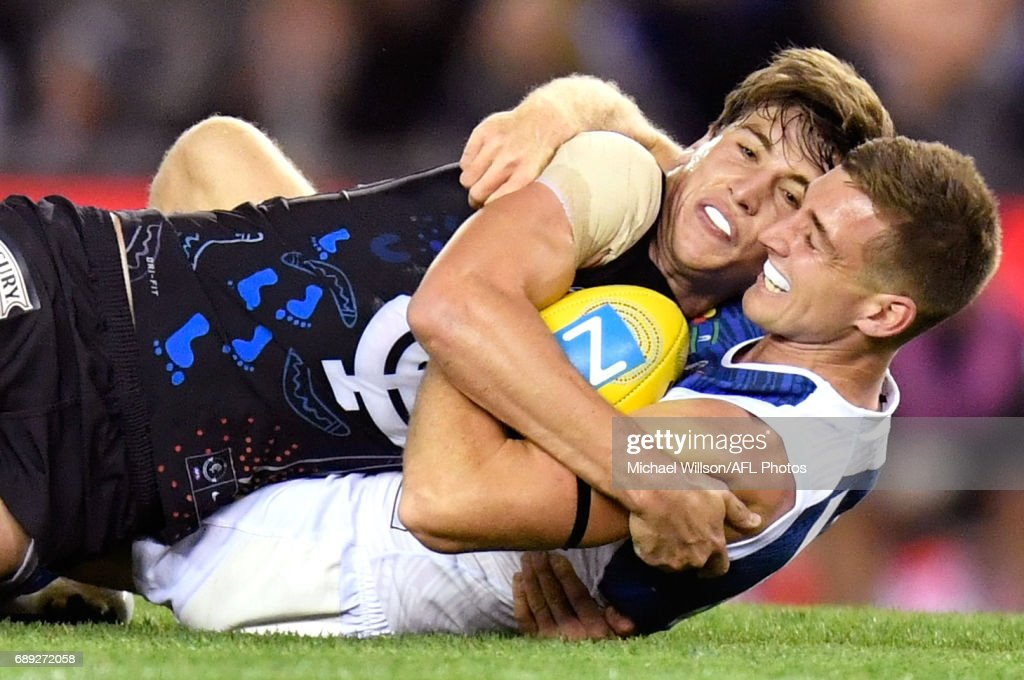Caleb Marchbank of the Blues is tackled by Shaun Atley of the Kangaroos during the 2017 AFL round 10 match between the Carlton Blues and the North Melbourne Kangaroos at Etihad Stadium on May 28, 2017 in Melbourne, Australia.