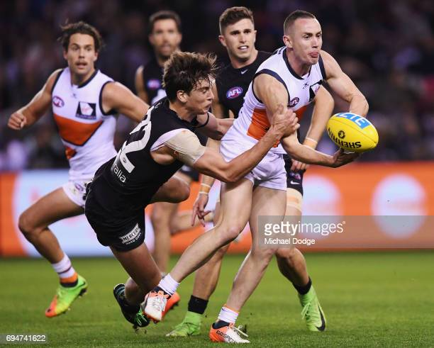 Caleb Marchbank of the Blues tackled Tom Scully of the Giants during the round 12 AFL match between the Carlton Blues and the Greater Western Sydney...