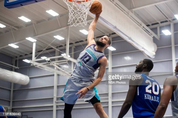 Caleb Martin of the Greensboro Swarm dunks the ball on Christ Koumadje of the Delaware Blue Coats during an NBA G League game on November 11, 2019 at...
