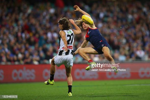 Caleb Poulter of the Magpies and Ed Langdon of the Demons compete for the ball during the round 13 AFL match between the Melbourne Demons and the...